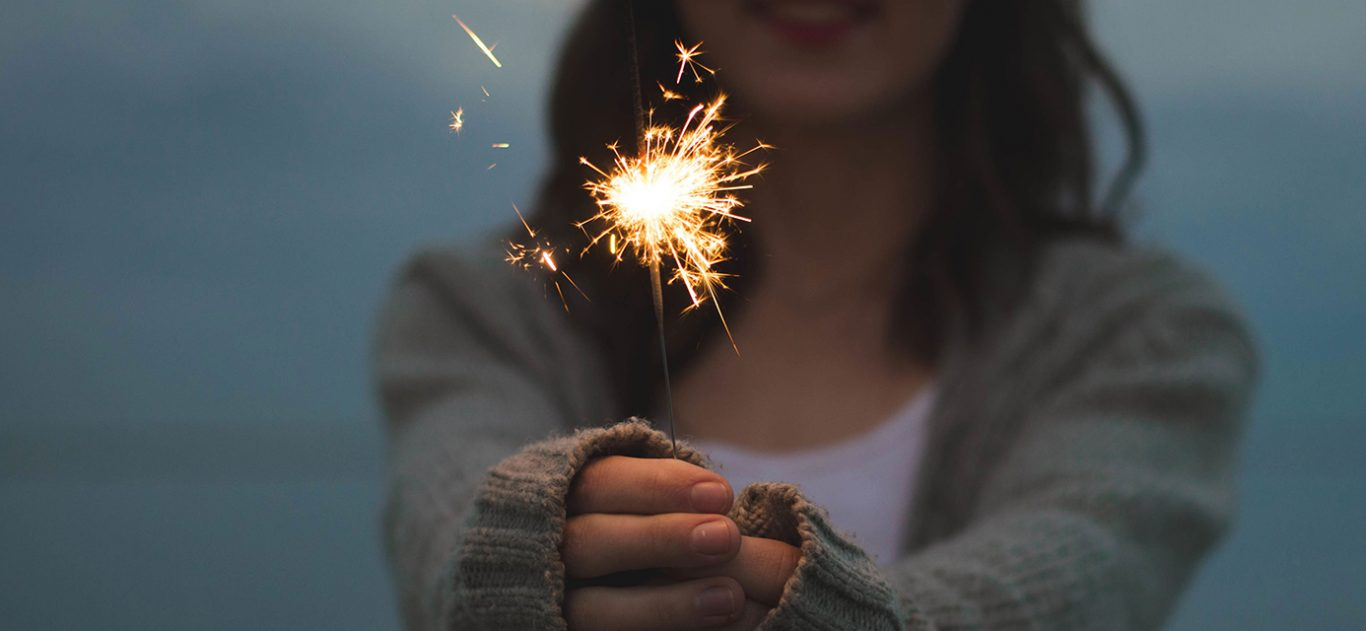 Close up of a lit sparkler in the hands of a young woman at dusk.