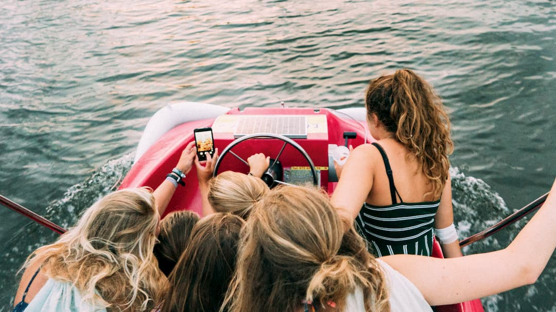 A group of teenage girls are packed into a small boat, while one of them reaches out an arm to take a group selfie.