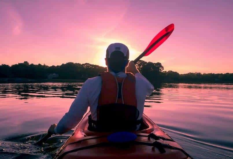 A young man kayaks across a still pond toward a sunset