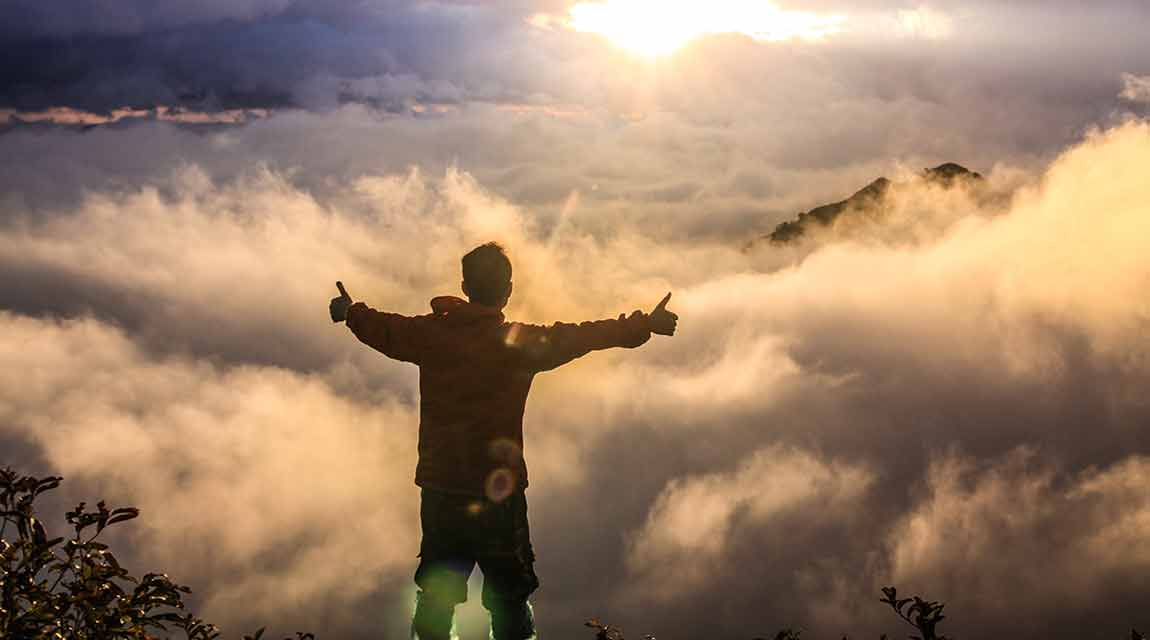 Boy improving mental health by standing atop a mountain