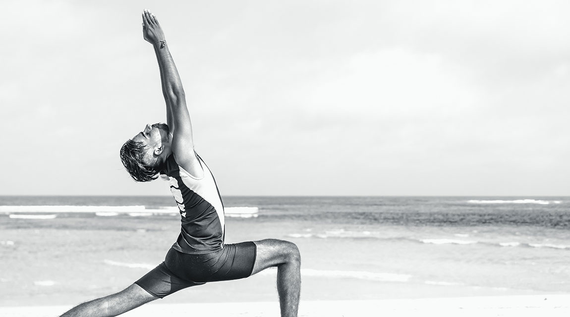Teen practicing yoga on the beach - Warrior 1 pose