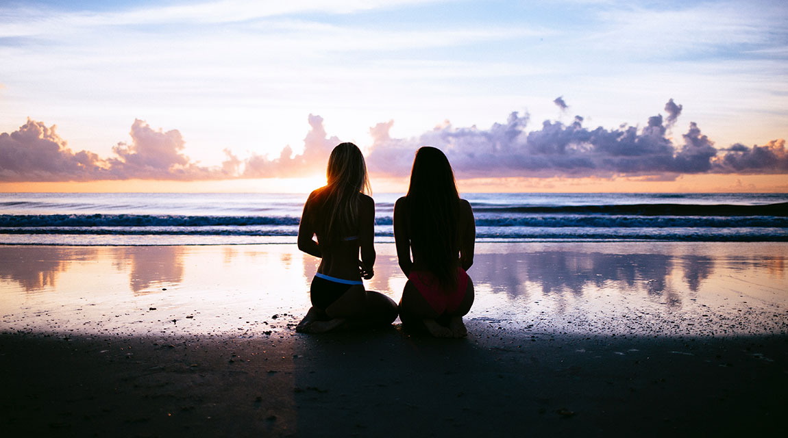Teen girls meditating on the beach