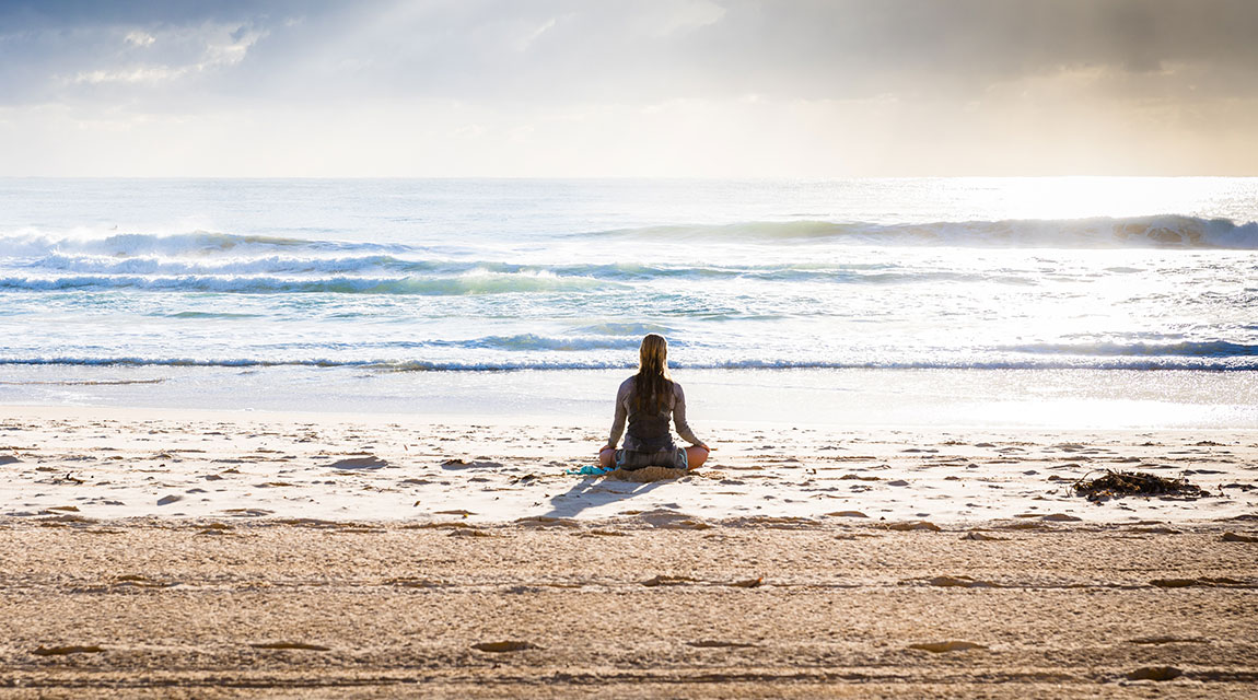 Girl on the beach during a meditation exercise