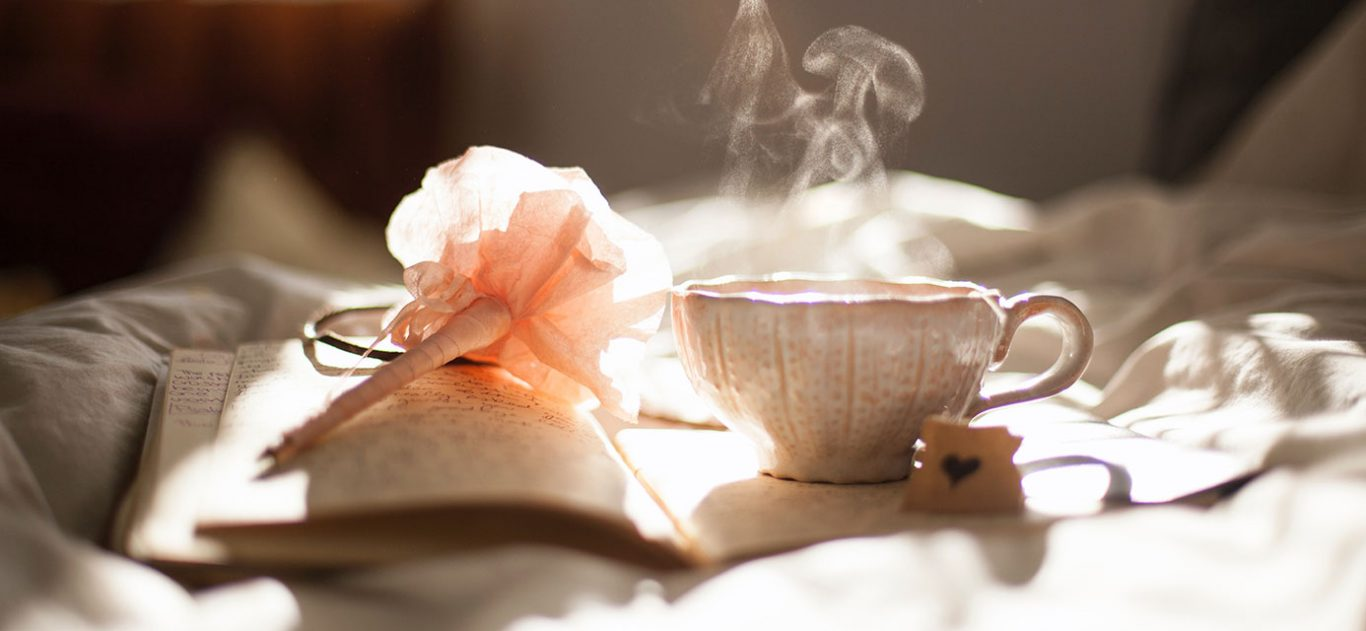 A cup of tea resting on an open journal