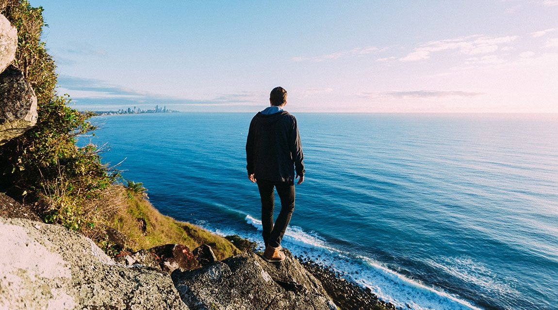 Boy standing on rocks by the ocean as part of his adventure therapy to treat his teenage depression