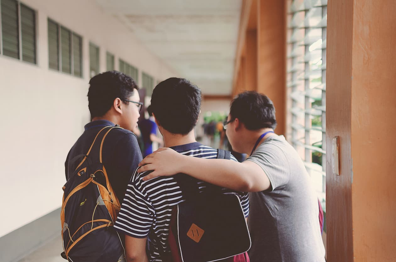three teens congregate in a school hallway, their backs to the camera as they start to walk together.